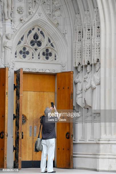 A passerby stops to take a mobile phone photo of a statue on the portal of Duke University Chapel seen here in middle right bearing the likeness of...