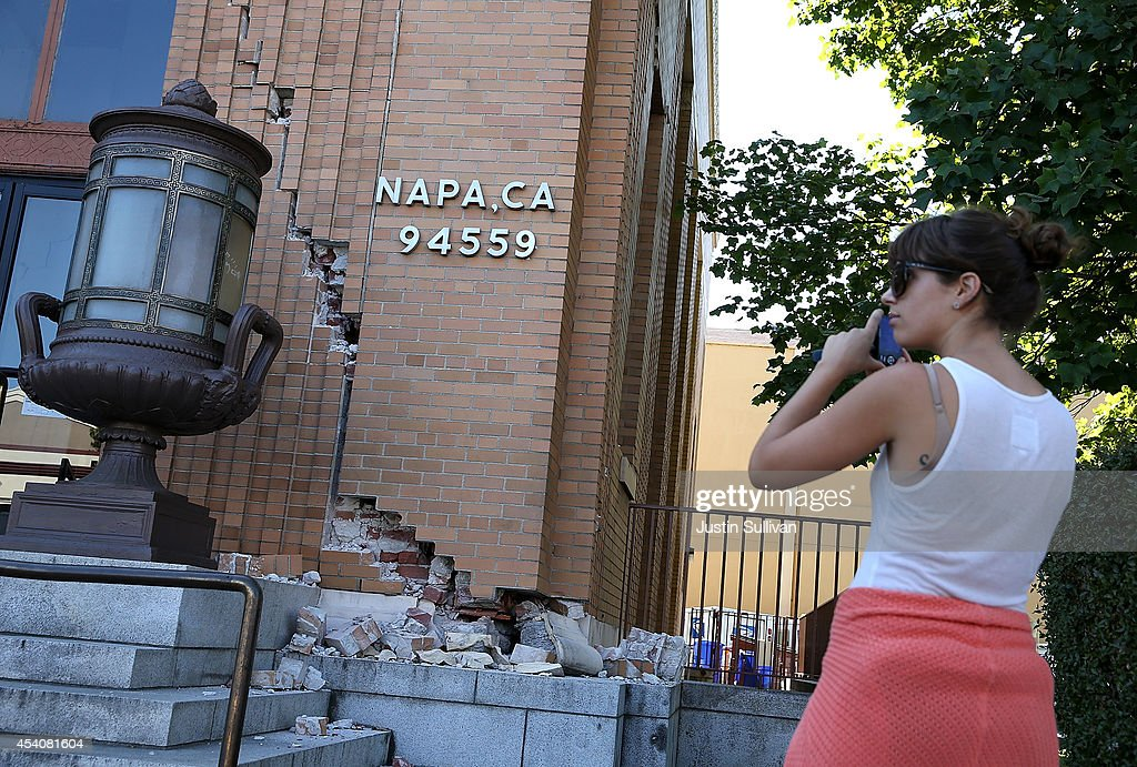 A passerby stops to take a picture of damage to the Napa post office following a reported 6.0 earthquake on August 24, 2014 in Napa, California. A 6.0 earthquake rocked the San Francisco Bay Area shortly after 3:00 am on Sunday morning causing damage to buildings and sending at least 70 people to a hospital with non-life threatening injuries.