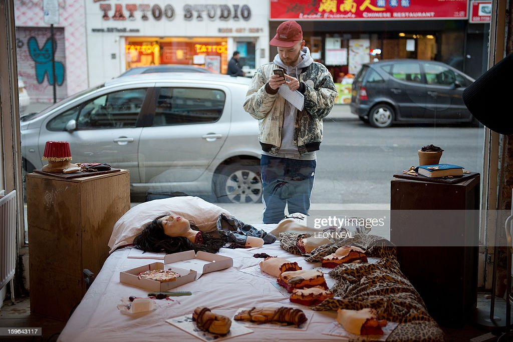 A passer-by takes a photograph of a selection of cakes in the shapes of severed body parts, made from entirely edible ingredients and displayed at a film set pop-up experience in east London on January 17, 2013. The event was held to promote the release of a new horror film 'The Helpers'. AFP PHOTO / LEON NEAL