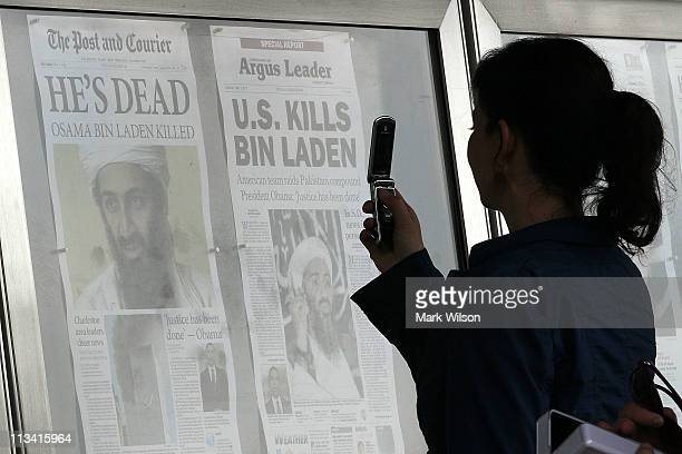 A passerby takes pictures of newspaper headlines reporting the death of Osama Bin Laden in front of the Newseum on May 2 2011 in Washington DC Last...