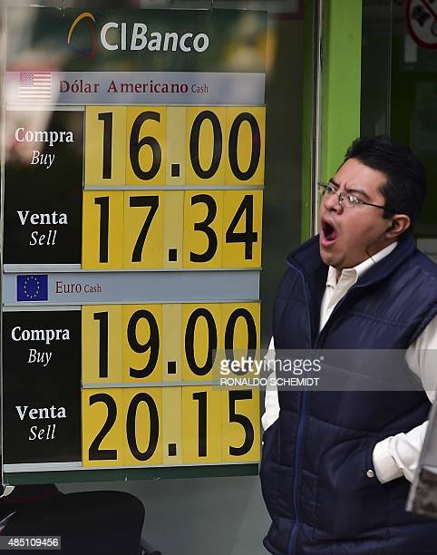 A passerby walks in front of a bank displaying a sign showing the exchange rate between the US dollar and the Mexican peso in Mexico City on August...