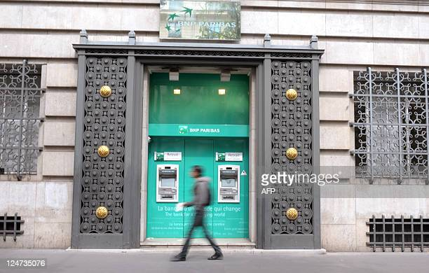 A passerby walks in front of an agency of French bank BNP Paribas in Paris on August 11 2011 The Paris stock market fell 123 percent in midday trade...