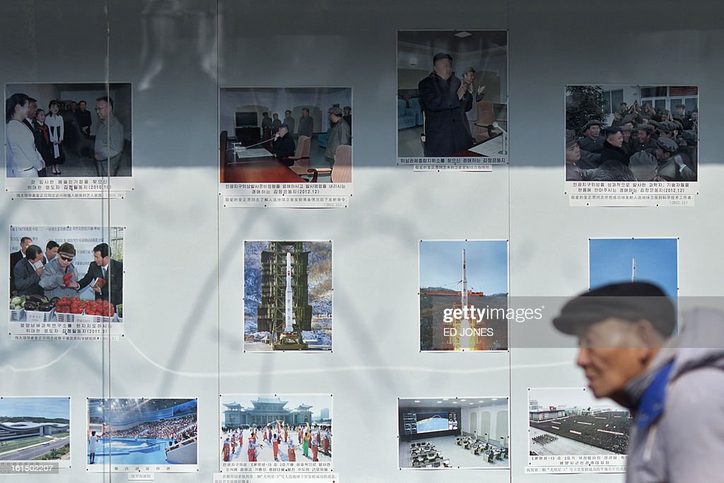 A passerby walks past images showing North Korean leader Kim Jong-Un and various rockets, re displayed outside the North Korean embassy in Beijing on Febraury 12, 2013. North Korea's apparent nuclear test had an explosive yield of between six and seven kilotons, South Korea's defence ministry said, revising its earlier estimate of 10 kilotons or more. Ministry spokesman Kim Min-Seok said seismic monitors had detected a tremor with a 4.9 magnitude emanating from the North's nuclear test site. AFP PHOTO / Ed Jones