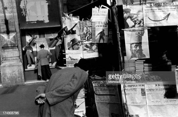 A passerbyer stoops and curiously looks at the headline of a daily newspaper on display in a kiosk Italy 1940