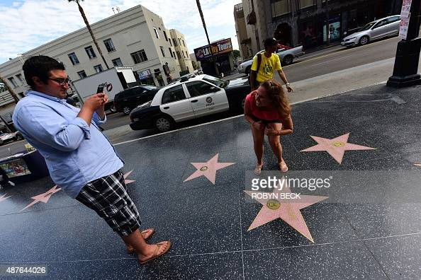Passerby's photograph Republican presidential candidate frontrunner Donald Trump's star on the Hollywood Walk of Fame on September 10 2015 in...