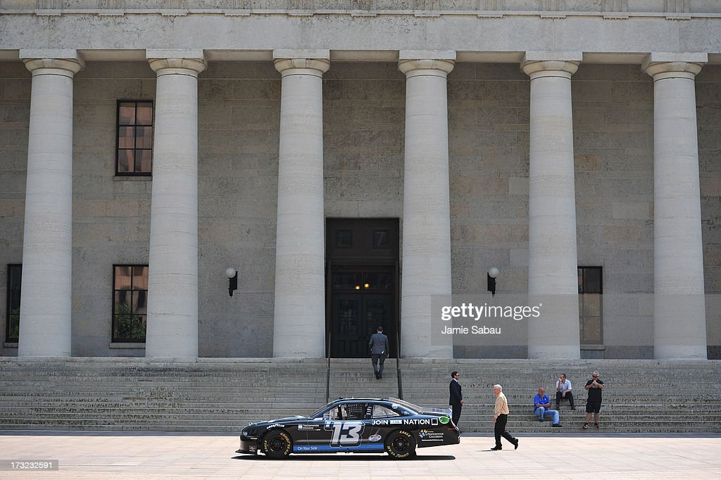 Passerbys take a closer look at a NASCAR car on display outside the Ohio Statehouse on July 10, 2013 in Columbus, Ohio.