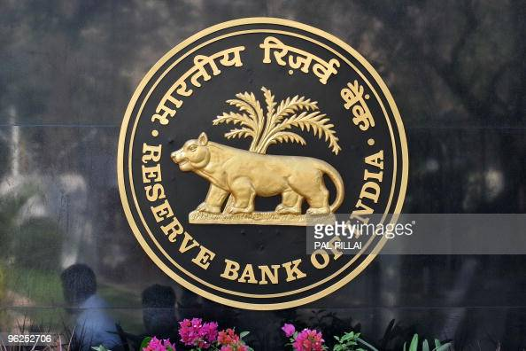Passers by are reflected on the logo of the Reserve Bank of India outside its headquarters in Mumbai on January 29 2010 India's central bank kept...