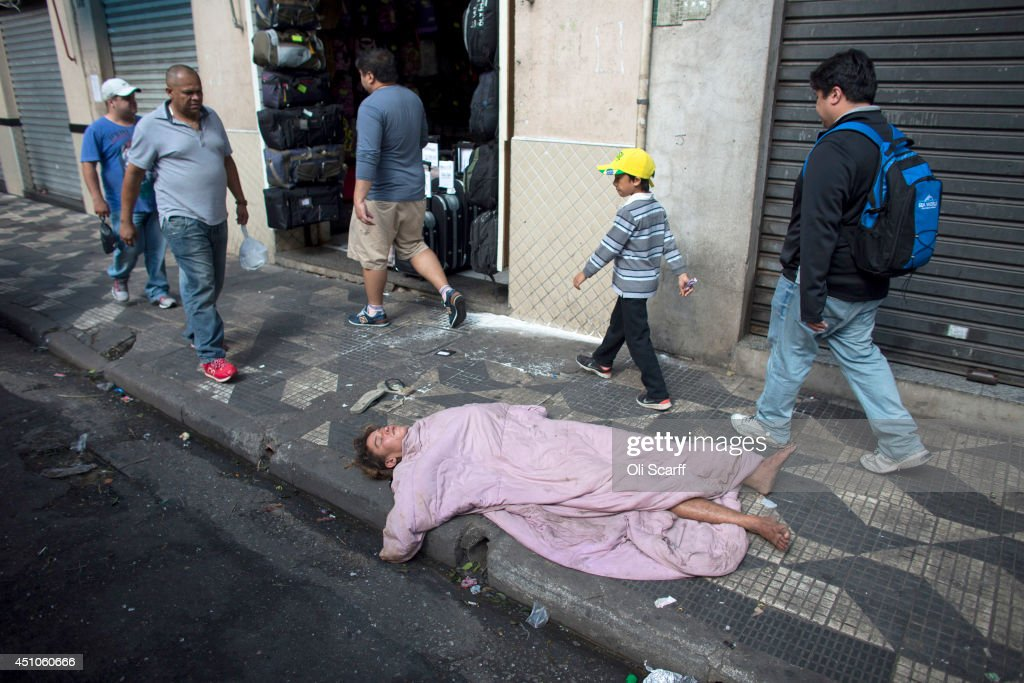 Passers by walk around a woman sleeping on the pavement near Sao Paulo's Mercado Municipal on June 22, 2014 in Sao Paulo, Brazil.