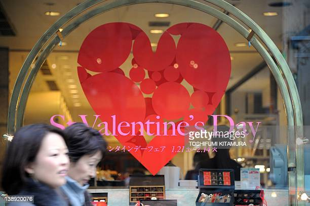 Passers by walk in front of a cake shop displaying a St Valentine's Day announcement at the Ginza district in Tokyo on February 14 2012 Valentine's...