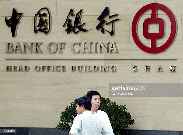 Passers by walk past the head office of the Bank of China in Beijing 12 June 2003 China Banking Regulatory Commission said a giant capital injection...