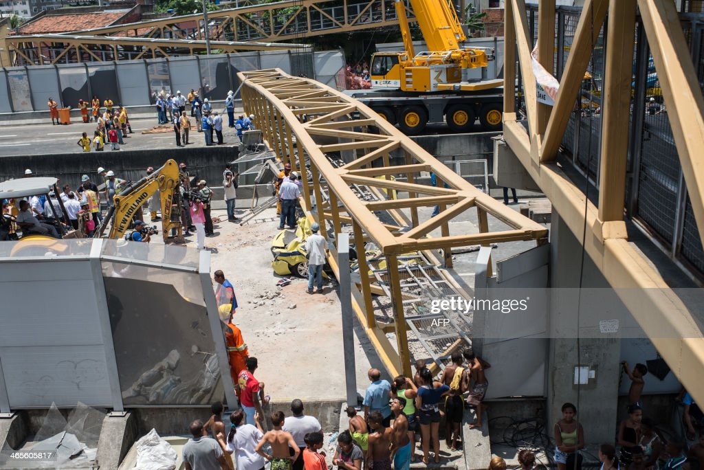 Passers by watch as rescuers work by a taxi crushed by a pedestrian bridge over the Linha Amarela (the yellow line) road in Rio de Janeiro, Brazil, on January 28, 2014. A pedestrian overpass spanning a busy road in Rio de Janeiro collapsed after being struck by a truck on Tuesday, killing four people below, officials said. At least four people were also injured in the accident. A pedestlian bridge falls on a taxi after a truck hit the bridge on the yellow line expressway in Rio de Janeiro, Brazil on January 28, 2014. 2014.