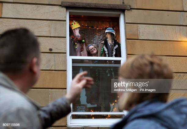Passers by watch Doctor Who fan Erica Quinn as she looks out from her window after she turned her house into her very own Tardis