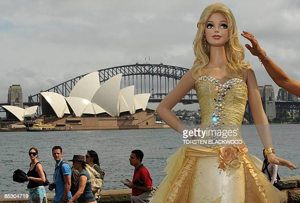 Passersby admire a 21 metre high 'Barbie doll' chocolate mud cake which was made to mark the 50th anniversary of the world's most popular doll on the...