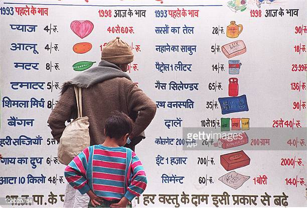 Passersby check comparative price lists of staple products between 1993 and 1998 printed on the back of a Congress Party election campaign vehicle 22...