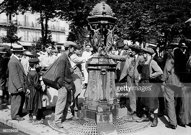 Passersby drinking in a Wallace fountain in Paris during a heat wave in June 1914