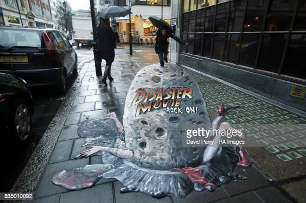 Passersby enjoy some 3D pavement art by artist Joe Hill in Great Portland Street London to mark the launch of Disaster Movie the latest slapstick...