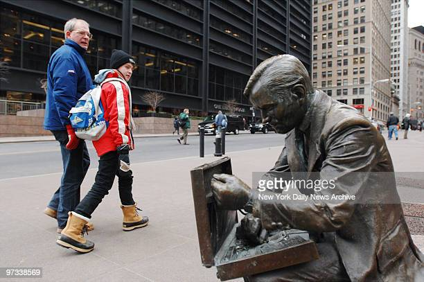 Passersby glance at the J Seward Johnson bronze sculpture of a businessman looking inside his briefcase entitled 'Double Check' as they stroll along...
