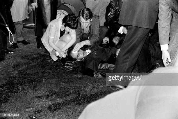 Passersby help an injured policeman following clashes betwenn riot police officers and students during a demonstration on May 4 1968 in Paris during...