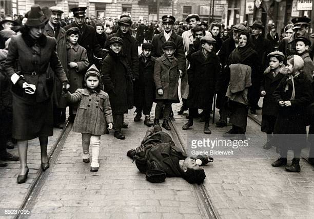 Passersby ignore a man lying in the street in the Warsaw Ghetto Poland 1941 The scene was possibly arranged