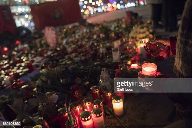 A passersby lights a candle at a memorial for the Christmas market terror attack victims at Breitscheidplatz on January 19 2017 in Berlin Germany On...