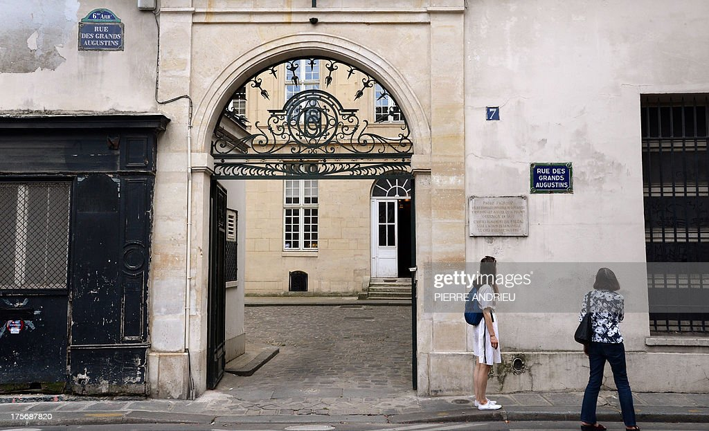 Passers-by look at a plaque, on August 6, 2013 in Paris, which informs that Spanish artist Pablo Picasso lived in this buiding, in a place called 'Grenier Picasso' (Picasso Attic) from 1936 to 1955. Threatened with imminent eviction, the association, dedicated to artistic education, that runs the Attic Picasso, asked the government today not to provide assistance to police force as a new lawsuit is pending. Picasso created one of his major works 'Guernica' in this studio in 1937.