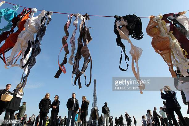 Passersby look at bras hung up by demonstrators on the Parvis des droits de l'homme in Paris on March 20 during a 'Spring cleaning' event called by...