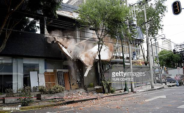 Passersby look at the demolishion of a damaged wall after a strong earthquake in Mexico City on May 8 2014 A strong 64magnitude earthquake rattled...