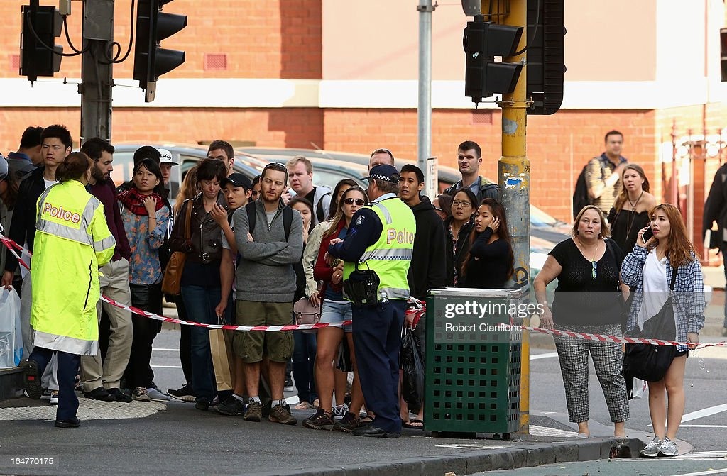 Passersby look on after a wall collapse on March 28, 2013 in Melbourne, Australia. Police have confirmed a man and a woman have died after a brick wall collapsed on Swanston street in Carlton in North Melbourne CBD.