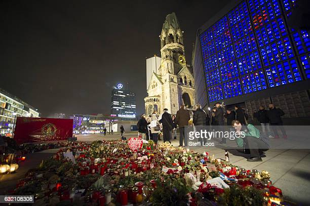 Passersby pause at a memorial for the Christmas market terror attack victims at Breitscheidplatz on January 19 2017 in Berlin Germany On December 19...