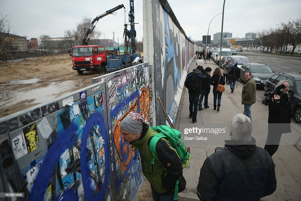 Passers-by peek into the construction site next to the East Side Gallery, which is the longest still-standing portion of the former Berlin Wall, where a new hotel is scheduled to be built on February 28, 2013 in Berlin, Germany. According to media reports the developer in charge of the project plans to remove an approximately 25-meter long piece of the Wall and transfer it elsewhere in order to allow access to the construction site. Critics, including East Side Gallery mural artists and Spree River embankment development opponents, decry the move, citing the East Side Gallery's status as a protected landmark and a major tourist attraction.