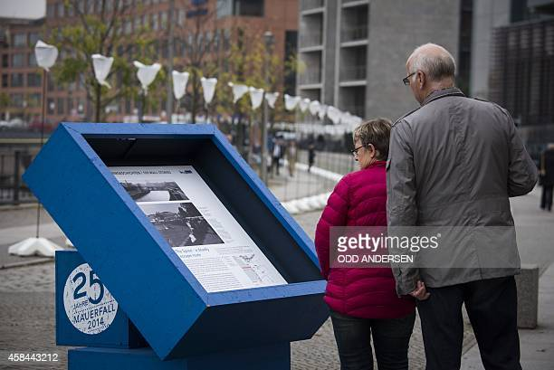 Passersby read historical facts at an information kiosk along a row of lanterns installed on the river Spree bank on the course of the former Berlin...