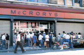 Passersby stand in front of a damaged store front looted in the wake of the New York City blackout Brooklyn New York New York July 14 1977