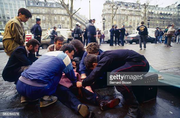Passersby stop to help victims of a bomb explosion in the PointShow boutique on the ChampsElysees killing 2 and wounding 28