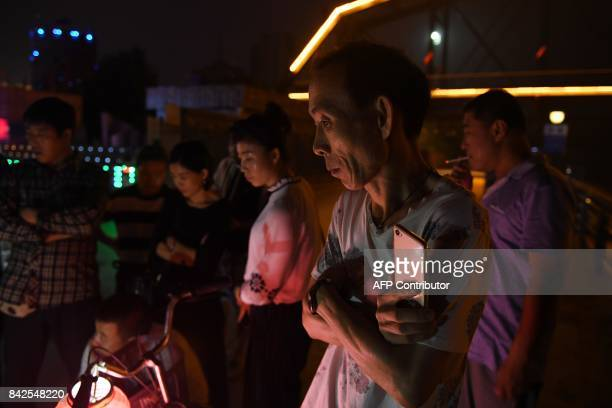 Passersby stop to watch a sidewalk entertainer in Dandong in China's northeast Liaoning province on the border with North Korea on September 4 2017...
