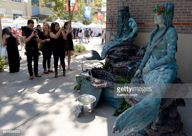 Passersby take a second look at live sculptures Christine Kuster right as the mermaid and Shane Borrillo as merman Crowds gather for the 14th annual...