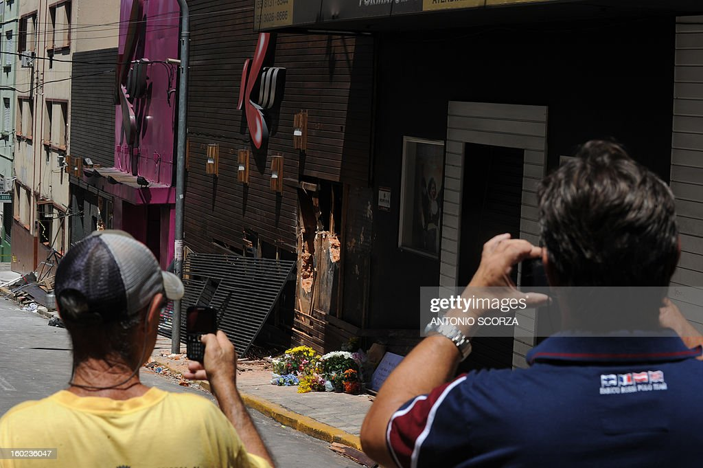 Passersby take snapshots of the facade of the Kiss nightclub where a blaze on the eve killed more than 230 people, on January 28, 2013 in Santa Maria, southern Brazil. AFP PHOTO ANTONIO SCORZA