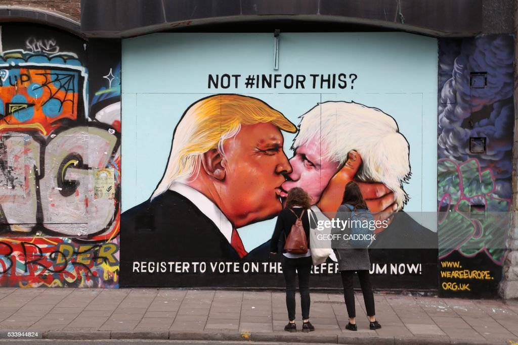 Passers-by view a mural showing likely US Republican presidential nominee Donald Trump (L) kissing the Former Mayor of London and Conservative MP, Boris Johnson, on the side of a building in Bristol, south west England on May 24, 2016. The mural in Bristol, southwest England, was commissioned by We Are Europe, a campaign group which wants Britain to remain in the European Union at the June 23 vote. / AFP / GEOFF