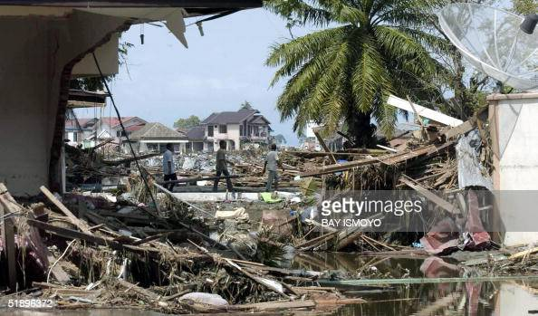Passersby walk amid debris of destroyed buildings 27 December 2004 in Banda Aceh after tidal waves hit the region The carnage suffered when Indonesia...