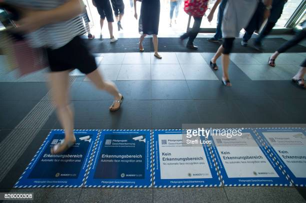 Passersby walk beside surveillance information signs which are part of facial recognition technology test at Berlin Suedkreuz station on August 3...