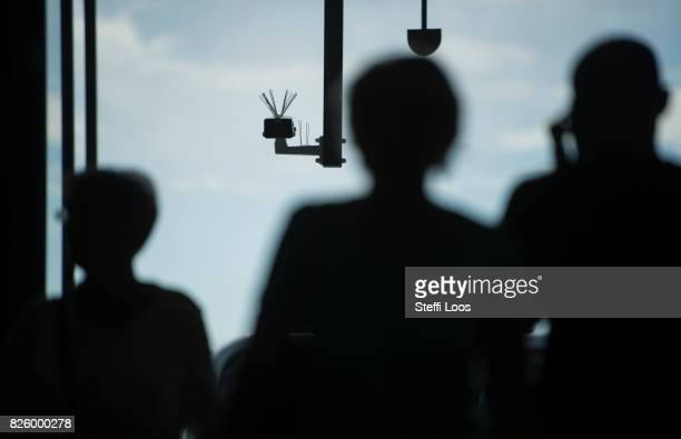 Passersby walk under a surveillance camera which is part of facial recognition technology test at Berlin Suedkreuz station on August 3 2017 in Berlin...