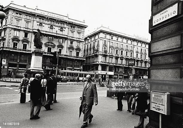 Passersby walking in Piazza Cordusio being crossed by trams Milan 1972