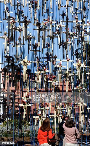 Passersby watch the crosses with their respective rosaries that for more than two decades marked the graves of fallen Argentine soldiers in the...