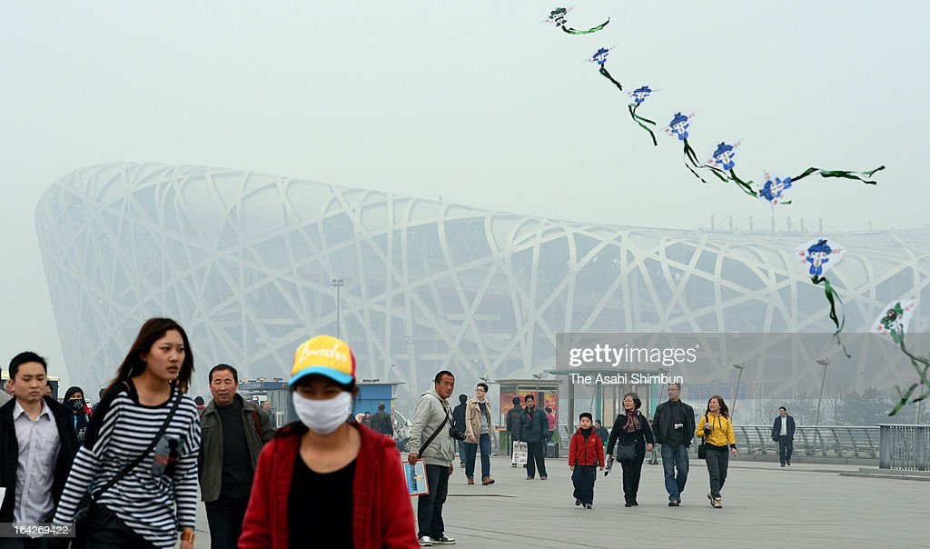 Passers-by were seen outside the Bird's Nest in haze on March 17, 2013 in Beijing, China.