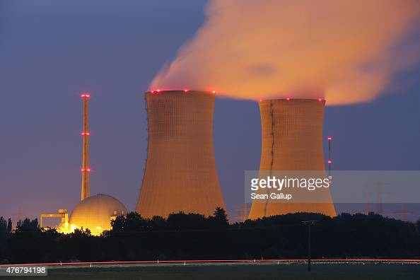 Passing cars leave a streak of light as steam rises from the cooling towers of the Grafenrheinfeld nuclear power plant at night on June 11 2015 near...