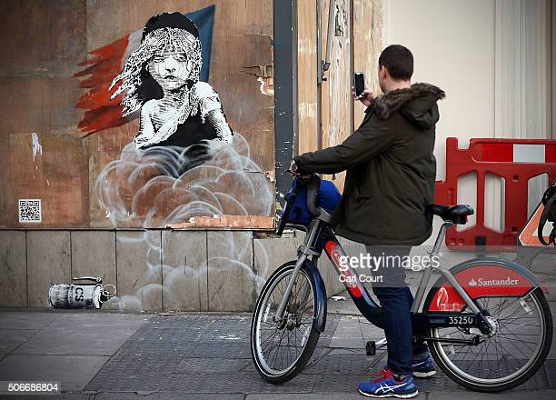 A passing cyclist takes a photograph of a Banksy artwork opposite the French embassy on January 25 2016 in London England The graffiti which depicts...