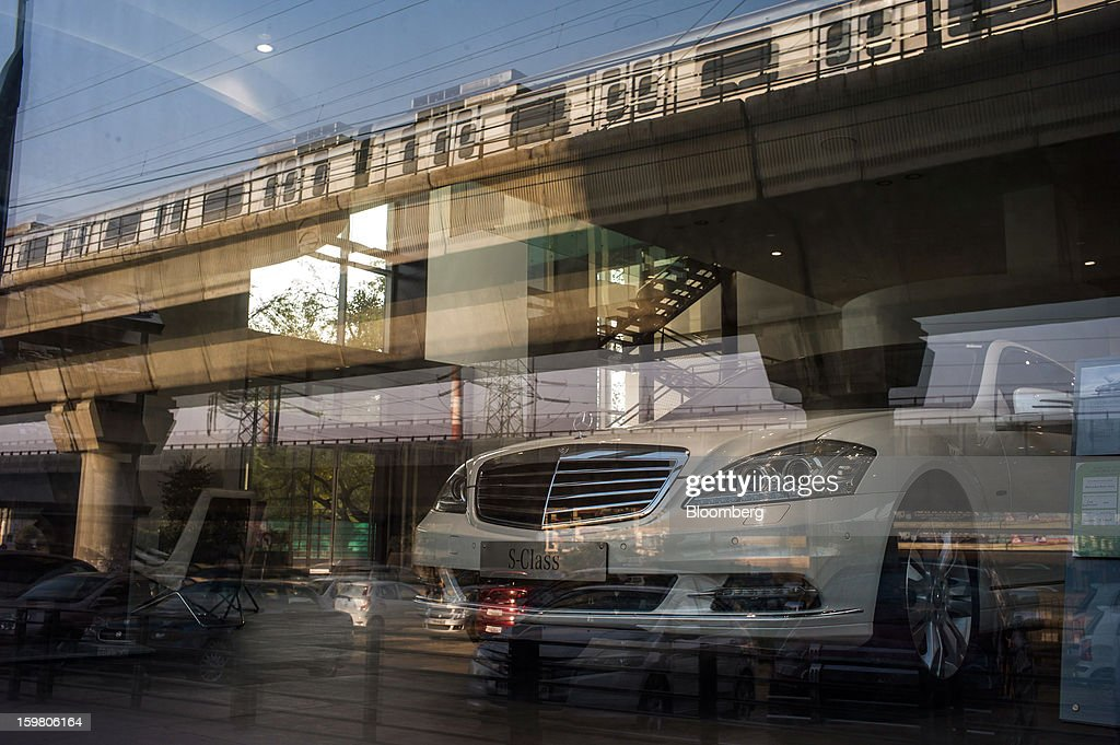 A passing Delhi Metro Rail Corp. train is reflected in a window behind which a Daimler AG Mercedes-Benz S-Class vehicle sits on display inside the newly opened T&T Motors Ltd. Mercedes-Benz India flagship dealership in New Delhi, India, on Saturday, Jan. 19, 2013. The Indian Finance Ministry projects Asia's third-largest economy will expand as little as 5.7 percent in the 12 months to March 31, which would be the weakest pace in a decade. Photographer: Sanjit Das/Bloomberg via Getty Images
