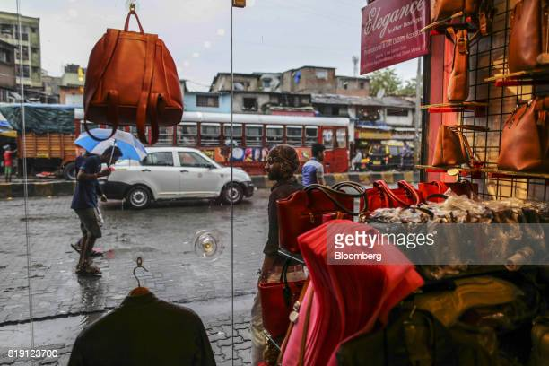 Passing pedestrians and traffic are seen through the window of a leather goods stores in the Dharavi area of Mumbai India on Tuesday July 18 2017...