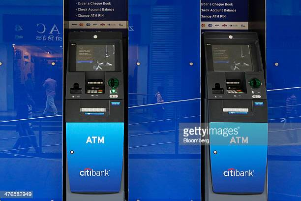 Passing pedestrians are reflected on the wall beside automated teller machines at a Citigroup Inc Citibank branch in Mumbai India on Friday Feb 21...