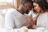 Peacefulness in us. Delighted peaceful positive African American couple sitting in the cafe and touching hands of each other while expressing peacefulness and love