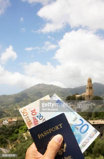 Passport and Euros overlooking rural landscape, Italy, Linguria, Italy